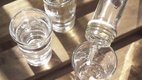 La vodka è versata in uno dei vetri sul movimento lento della tavola archivi video