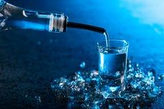 La vodka versée dans un verre s'est allumée avec le contre-jour bleu image libre de droits