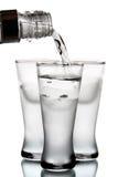 La vodka versa in vetro Fotografia Stock
