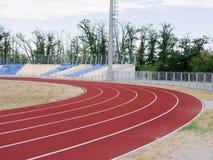 La voie courante rouge, l'herbe colorée et vident des supports au stade, sur le ciel bleu Concept de sport et de forme physique Photo libre de droits