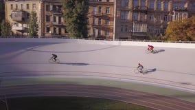 La voie dans la ville, maisons à l'arrière-plan, trois cyclistes concurrencent sur la voie, trains pour la grande course, été banque de vidéos