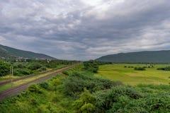 La voie de chemin de fer droite va à l'horizon dans le paysage vert sous le ciel bleu avec des nuages photographie stock