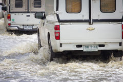 La voiture éclabousse par un grand magma sur une rue inondée Photos stock