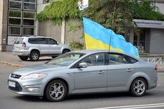 La voiture avec le drapeau ukrainien va sur la route Image stock