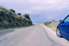 la voiture bleue du côté d'une route de montagne, donnant sur le ser Photos stock