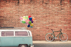 La voiture classique dans la ville avec le ballon coloré sur le toit s'est garée sur la route à urbain Images libres de droits