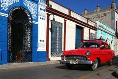 La voiture classique rouge passe devant un bâtiment bleu et blanc Image libre de droits