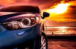 La voiture compacte de SUV avec le sport, moderne bleus, et la conception de luxe se sont garés sur la route bétonnée par la mer  Image stock