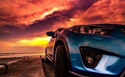 La voiture compacte de SUV avec le sport, moderne bleus, et la conception de luxe se sont garés sur la route bétonnée par la mer  Images stock
