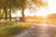 La voiture conduit le long d'une route rurale étroite image stock