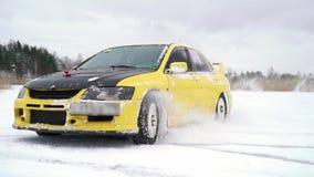 La voiture conduit par la voie glaciale sur le lac couvert par neige à l'hiver Courses d'automobiles de sport sur la voie de cour banque de vidéos
