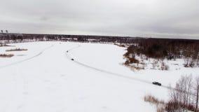 La voiture conduit par la voie glaciale sur le lac couvert par neige à l'hiver Silhouette d'homme se recroquevillant d'affaires C banque de vidéos