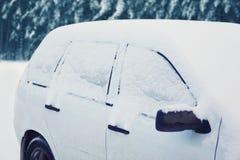 La voiture congelée a couvert la neige dans le jour d'hiver Photographie stock libre de droits