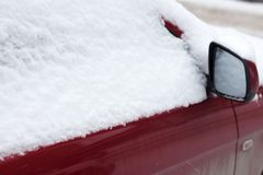 La voiture congelée a couvert la neige dans le jour d'hiver, le pare-brise de fenêtre avant de vue et le capot sur le fond neigeu Photographie stock libre de droits