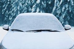 La voiture congelée d'hiver a couvert la neige, le pare-brise de fenêtre avant de vue et le capot sur neigeux Image stock