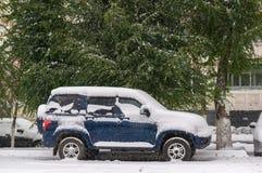 La voiture couverte de neige se tient sous les arbres verts pendant le sno Photo stock