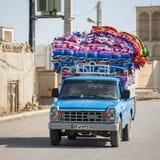 La voiture de collecte chargée avec les matelas colorés monte autour des rues image stock