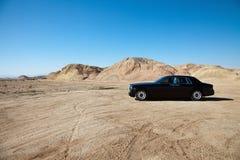 La voiture de luxe a garé sur la route non pavée près des montagnes photographie stock