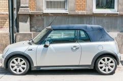 La voiture de Mini Cooper S de cabriolet avec le toit convertible s'est garée sur la rue dans la ville Images stock