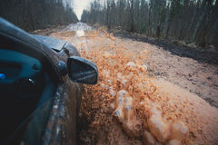 La voiture de Suv 4wd monte par le magma boueux, route tous terrains de voie, avec une grande éclaboussure, pendant une concurren Photos libres de droits