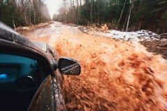 La voiture de Suv 4wd monte par le magma boueux, route tous terrains de voie, avec une grande éclaboussure, pendant une concurren Photo stock