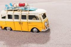 La voiture de vintage avec des planches de surf et la délivrance sonnent sur la plage Images stock