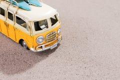 La voiture de vintage avec des planches de surf et la délivrance sonnent sur la plage Image stock