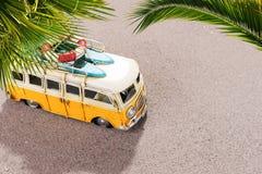 La voiture de vintage avec des planches de surf et la délivrance sonnent sur la plage Image libre de droits