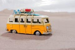La voiture de vintage avec des planches de surf et la délivrance sonnent sur la plage Photographie stock