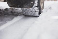 La voiture est sur une route couverte de neige d'hiver La roue est en gros plan Image libre de droits