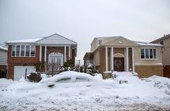 La voiture et la maison sous la neige après les tempêtes massives d'hiver heurte au nord-est Images libres de droits