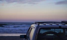 La voiture a garé sur la plage faisant face à un lever de soleil Photos stock