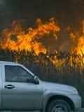 La voiture monte rapidement autour d'un feu énorme Photographie stock