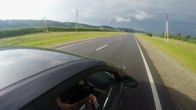 La voiture monte sur une route de montagne pendant l'été banque de vidéos