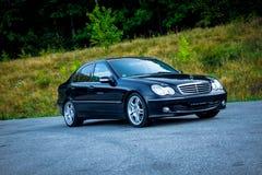 La voiture noire de luxe de berline a garé dans le parking près d'un amortisseur avant forêt-droit Photographie stock