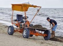 La voiture pour la récupération de place de la plage Nettoyant sur la plage, la plage propre de la boue et les déchets Image libre de droits
