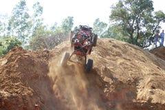 La voiture rouge construisant contre la colline très raide, les roues avant suspen Photographie stock