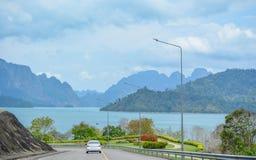 La voiture roule sur la route avec vue sur les montagnes et le barrage images libres de droits