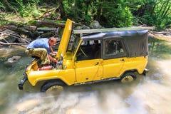 La voiture russe tous terrains a collé en rivière de montagne à la panne soudaine tout en jeeping Conducteur fixant l'automobile  Photos libres de droits