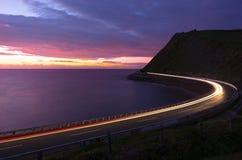 La voiture s'allume au crépuscule sur la route à côté de la côte de Zumaia photographie stock