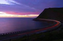 La voiture s'allume au crépuscule sur la route à côté de la côte de Zumaia images stock
