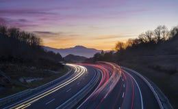 La voiture s'allume la nuit sur la route allant à la ville de Donostia Image stock
