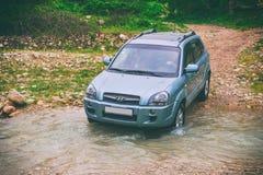 La voiture se déplace par la rivière de montagne Photos stock