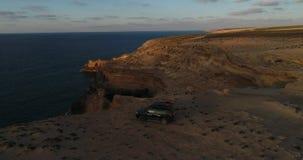 La voiture se tient sur le rivage de l'oc?an Silhouette d'homme se recroquevillant d'affaires banque de vidéos