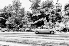 La voiture sur la route goudronnée d'hiver a couvert la neige Photographie stock