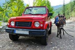 La voiture tous terrains 4x4 CONTRE l'âne - voyagez dans les montagnes Photo libre de droits