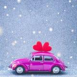 La voiture ultra-violette de jouet porte le coeur rouge d'amour sur le toit Concept d'invitation de carte postale de mariage ou d Photo stock
