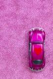 La voiture ultra-violette de jouet porte le coeur rouge d'amour sur le toit Concept d'invitation de carte postale de mariage ou d Image libre de droits