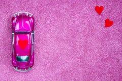 La voiture ultra-violette de jouet porte le coeur rouge d'amour sur le toit Concept d'invitation de carte postale de mariage ou d Photo libre de droits