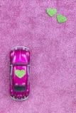 La voiture ultra-violette de jouet porte le coeur vert d'amour sur le toit Concept d'invitation de carte postale de mariage ou de Photo libre de droits